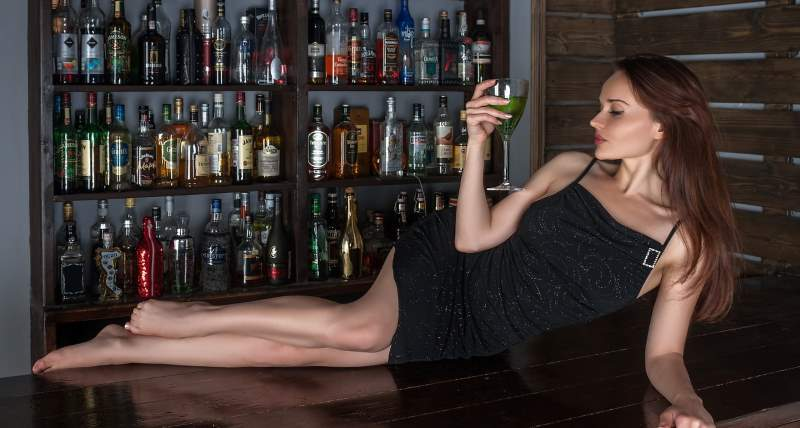 Will she be testing you this evening? Will you pass it? Why is this woman laying on the bar?